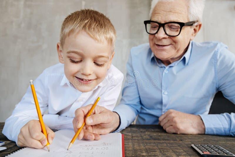 Восторженный славный человек уча его математике внука стоковое изображение rf