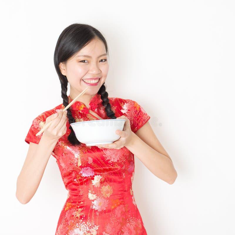 Восточная женщина в красном cheongsam есть с палочками стоковое изображение rf