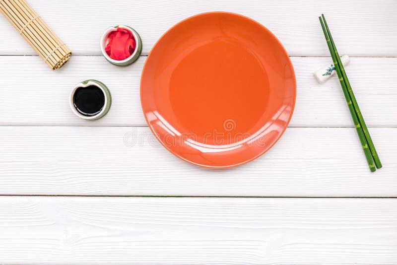 Восточная таблица настроенная с плитой и бамбуковыми ручками для суш и maki на белом космосе взгляда сверху предпосылки для текст стоковые фото