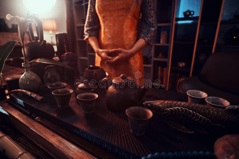 Восточный мастер в кимоно стоя рядом с таблицей с набором для делать чай и аксессуары в темной комнате с a стоковые фото