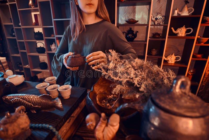 Восточный мастер нося серое платье держа чайник в темной комнате с деревянным интерьером Традиция, здоровье стоковые изображения rf