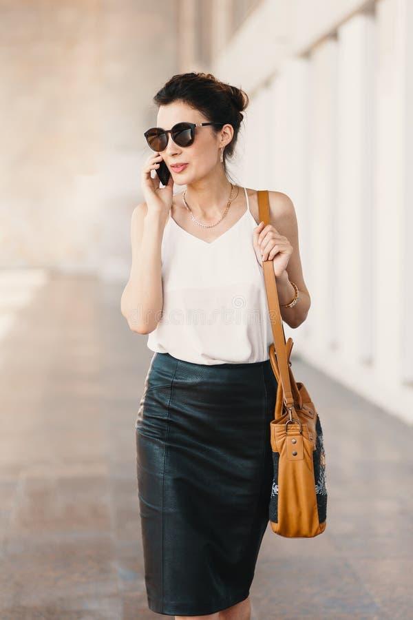 Восхитительная бизнес-леди в кожаной блузке юбки и шелка говоря по телефону outdoors стоковые изображения