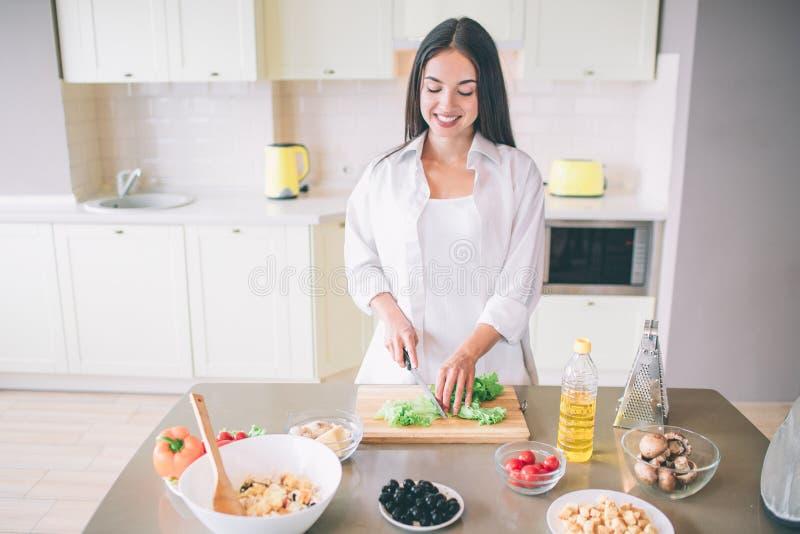 Восхитительная и счастливая молодая женщина стоит и варит в кухне Она режет салат на деревянной доске Девушка имеет ingrediends ч стоковая фотография