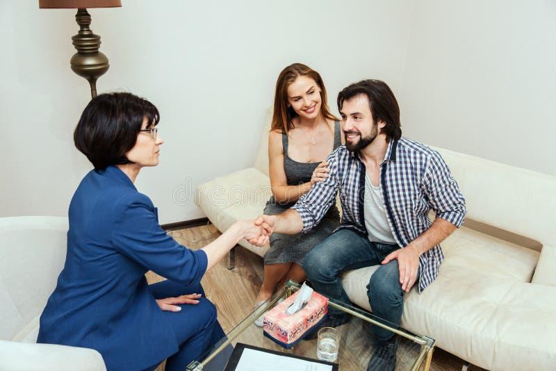 Восхитительная и счастливая пожененная пара сидит совместно Гай смотрит доктора и трясет ее руку Молодая женщина стоковые изображения rf