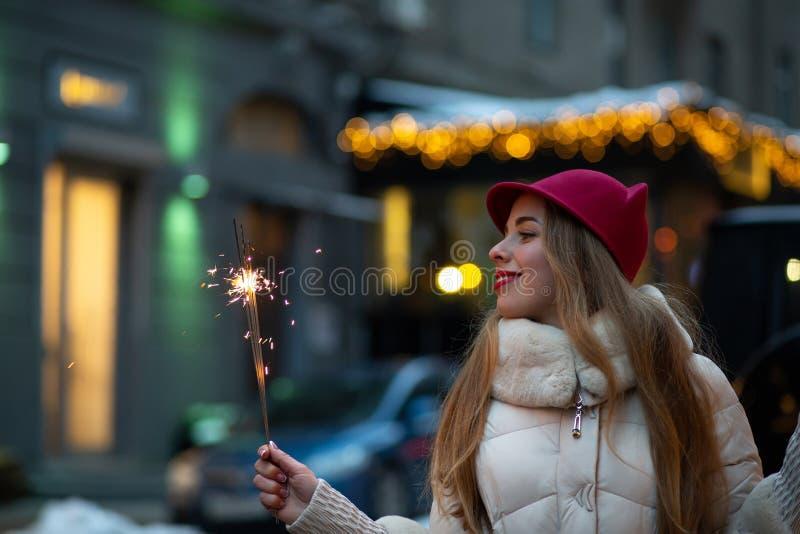 Восхитительная молодая дама нося смешную шляпу и пальто зимы празднуя рождество на улице с бенгальскими огнями Космос для текста стоковые изображения rf