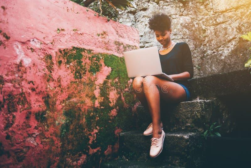 Восхитительная молодая чернокожая женщина с netbook на каменистом шаге стоковые изображения rf