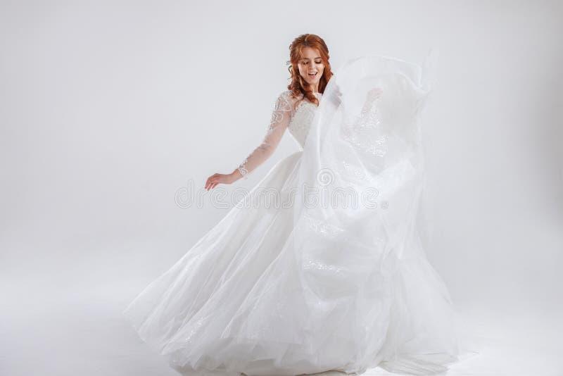 Восхитительная рыжеволосая невеста в роскошном платье Светлая предпосылка стоковые фото