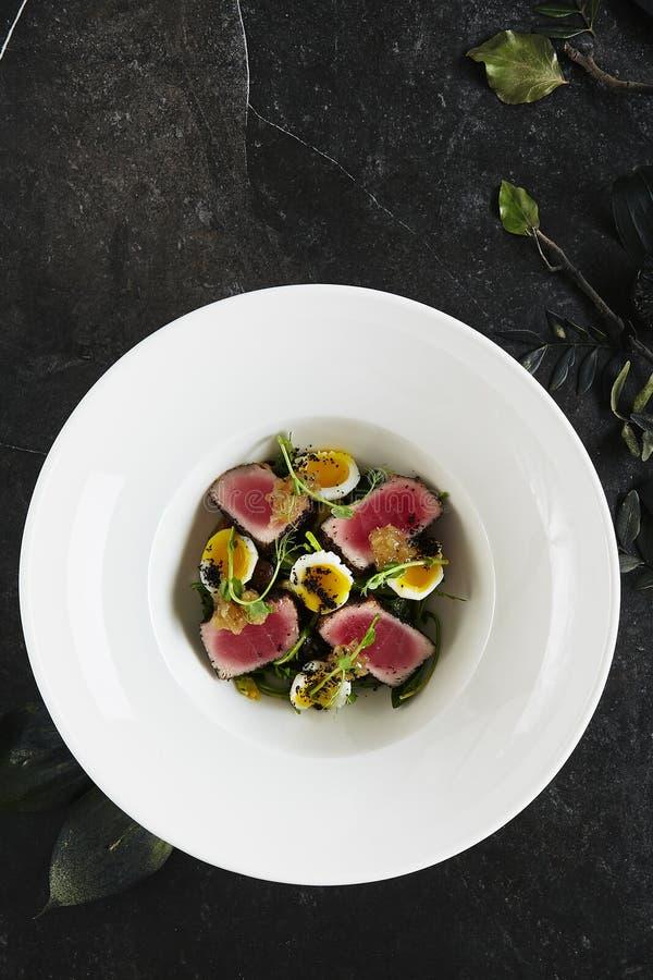 Восхитительная служа белая плита ресторана салата филе тунца с яйцами и сальсой триперсток от сладкого взгляда сверху томатов стоковые изображения