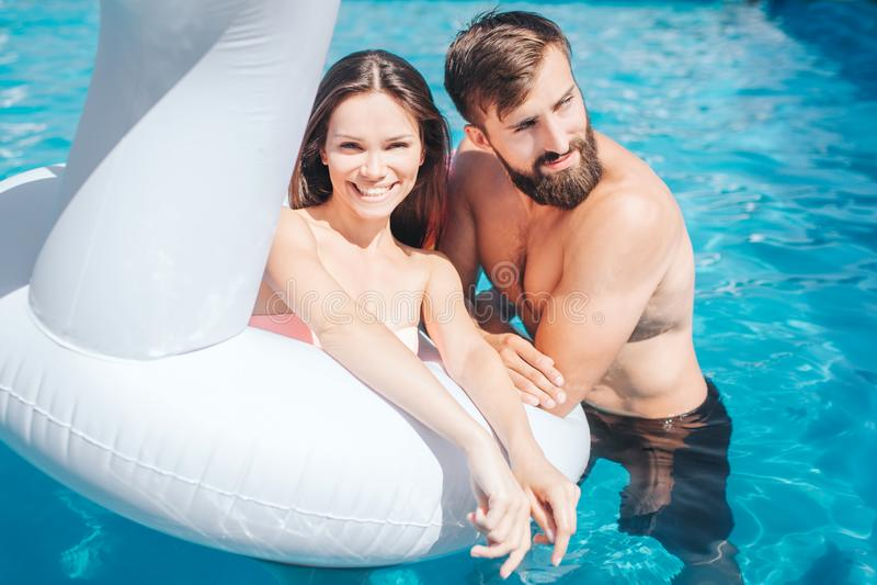 Восхитительное изображение пар в бассейне Девушка сидит тюфяк и взгляд inair на камере Она усмехается Гай полагается к стоковое изображение