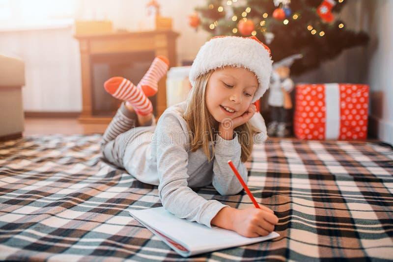 Восхитительный ребенок лежит на одеяле и пишет письмо Она держит другую руку под подбородком и держит ноги пересеченный девушка стоковая фотография rf