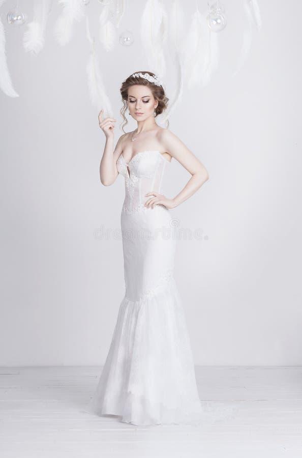 Восхитительная молодая и мечтательная невеста в длинном роскошном платье свадьбы шнурка стоковая фотография rf