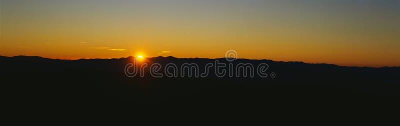 Восход солнца над большими закоптелыми горами стоковая фотография