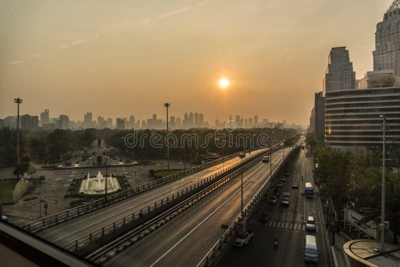 Восход солнца над горизонтом города Бангкока Высокие здания за парком с шоссе на переднем плане стоковое фото