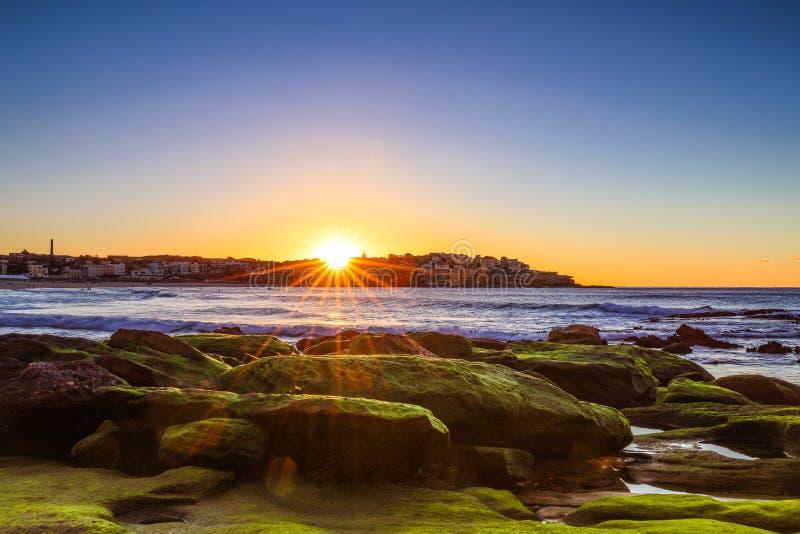 Восход солнца над океаном и мхом покрыл утесы против голубого неба стоковая фотография