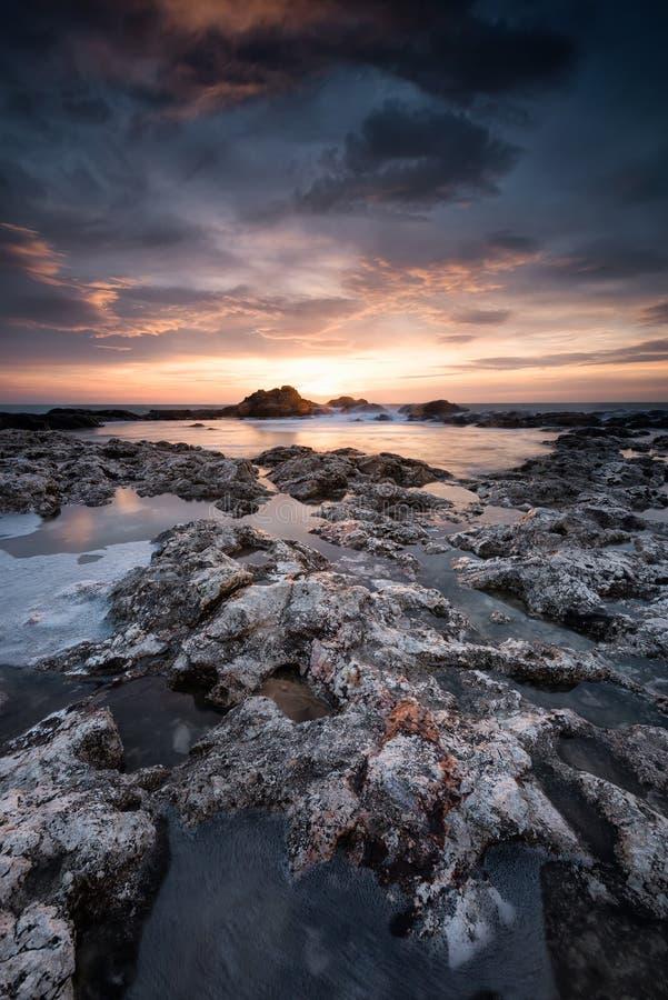 Восход солнца на скалистом пляже стоковые фото