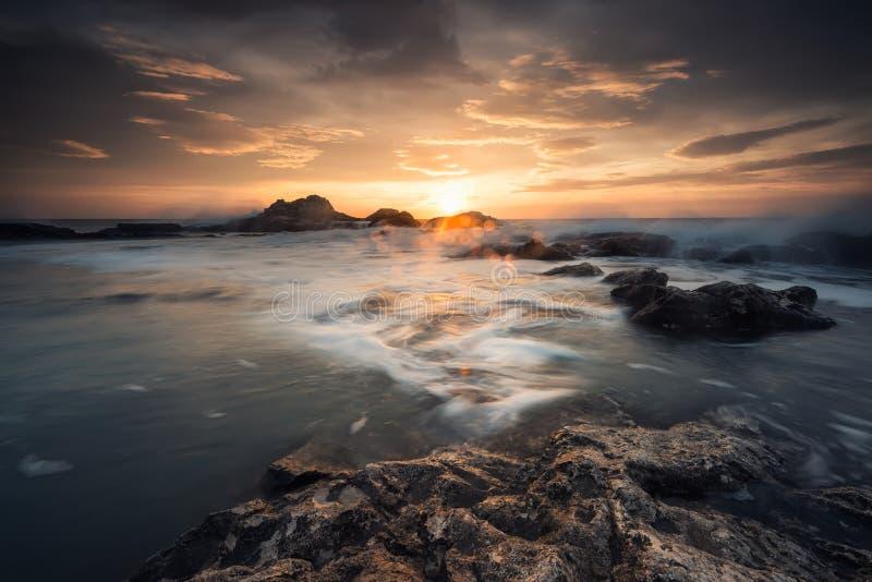 Восход солнца на скалистом пляже стоковые фотографии rf