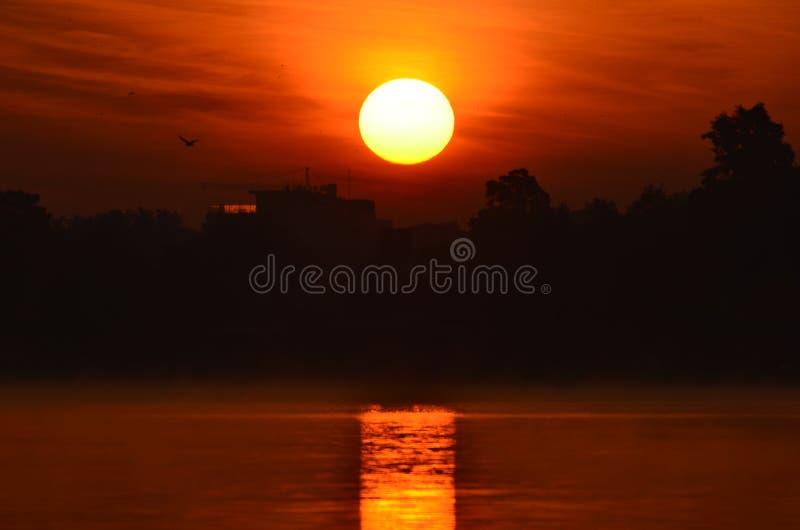 Восход солнца поднимая над озером города стоковое фото rf