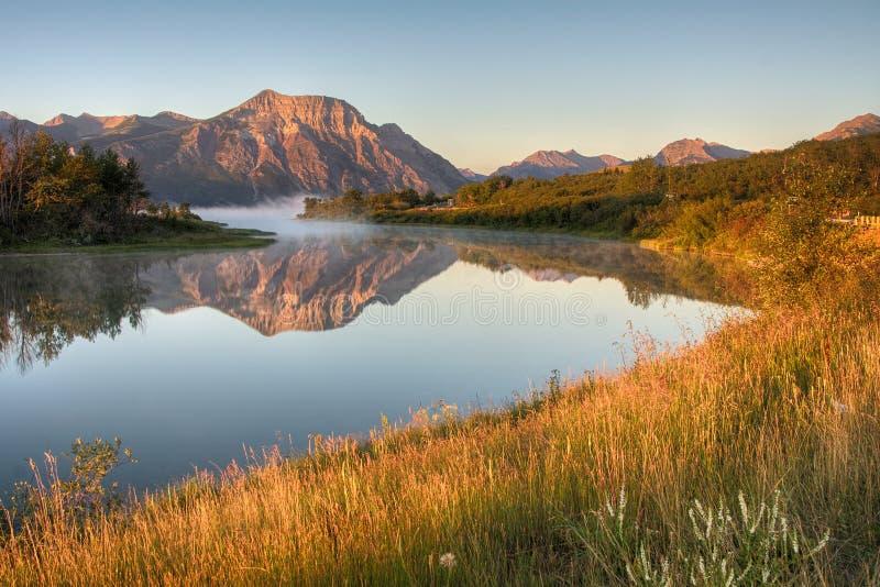 Восход солнца скалистой горы над водой стоковое фото rf