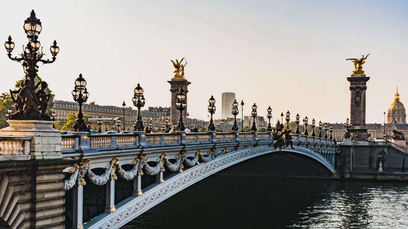 Восход солнца утра против света на красивом Pont Александр III в Париже стоковая фотография