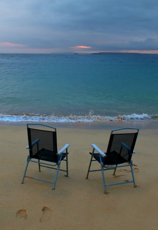 Восход солнца, море и стулья стоковая фотография