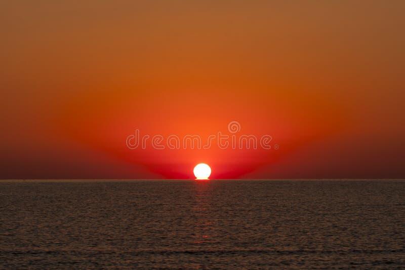 Восход солнца на море с водой Солнця касающей стоковые изображения