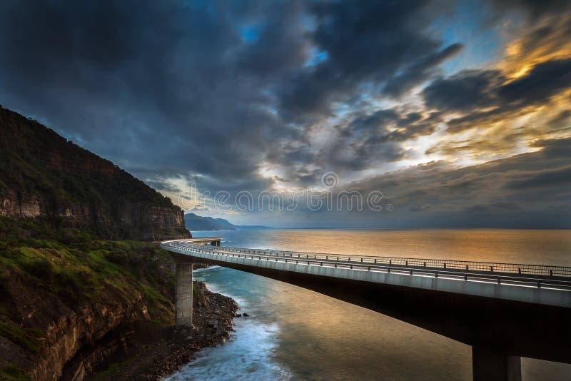 Восход солнца над мостом скалы моря стоковое изображение rf