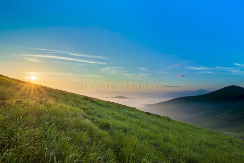 Восход солнца над холмами в горах с wi зеленой травы и голубого неба стоковое фото rf