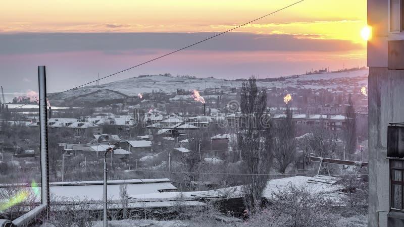 Восходящее солнце в городе снега и над фабрикой стоковые фотографии rf