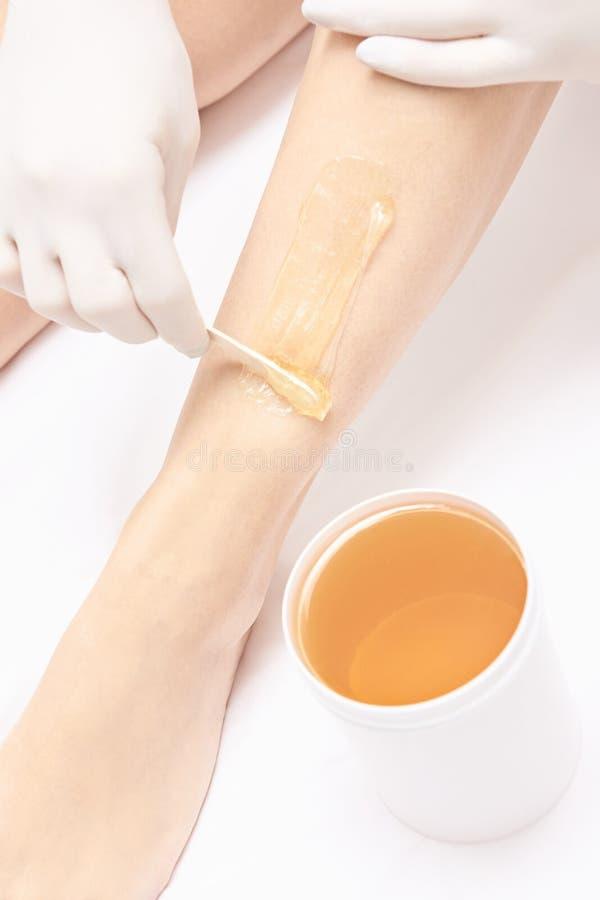 Вощить ногу женщины Удаление волос сахара epilation обслуживания лазера Процедура по beautician воска салона стоковое фото