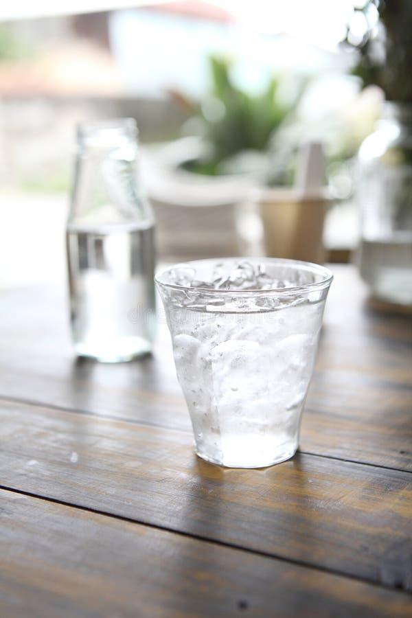 Вода в стекле в деревянной предпосылке стоковые фотографии rf