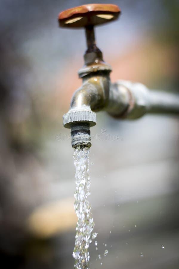 Вода из крана и пускает значение воды по трубам стоковое изображение