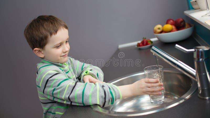 Вода из крана мальчика лить в стекло стоковое изображение rf