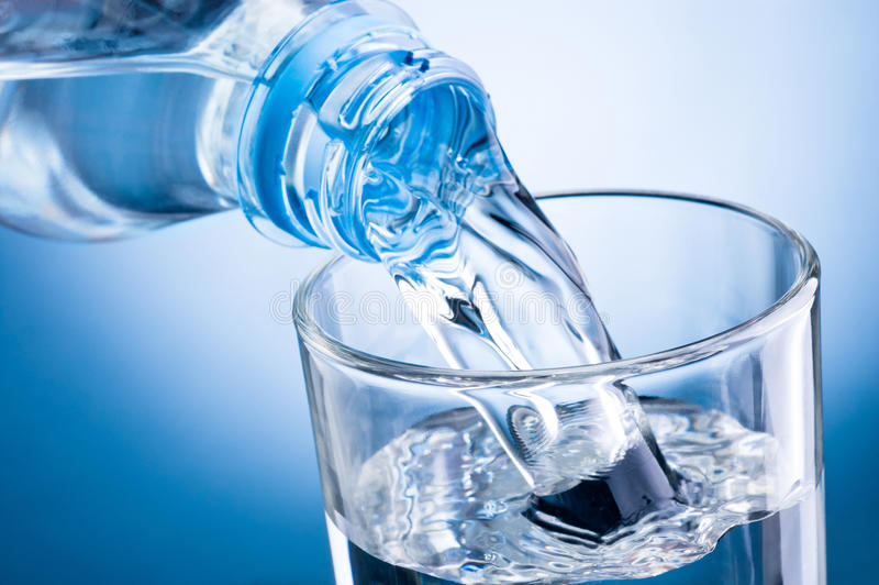 Вода конца-вверх лить от бутылки в стекло на голубой предпосылке стоковое изображение