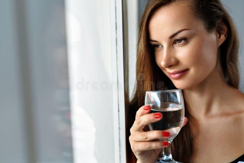 Вода питья Усмехаясь питьевая вода женщины Диета Здоровый уклад жизни стоковая фотография