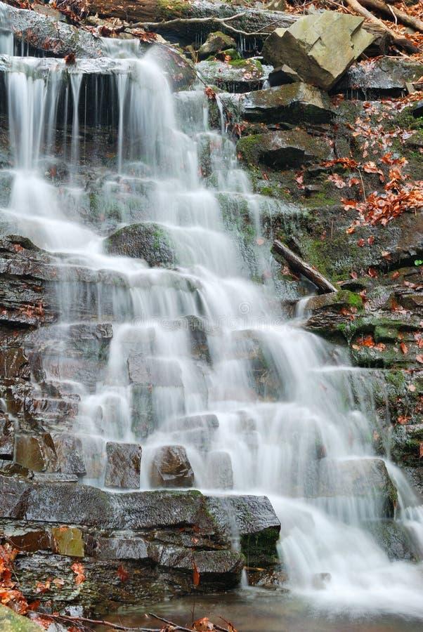 Вода пропуская над утесами в каскаде водопада стоковые изображения rf