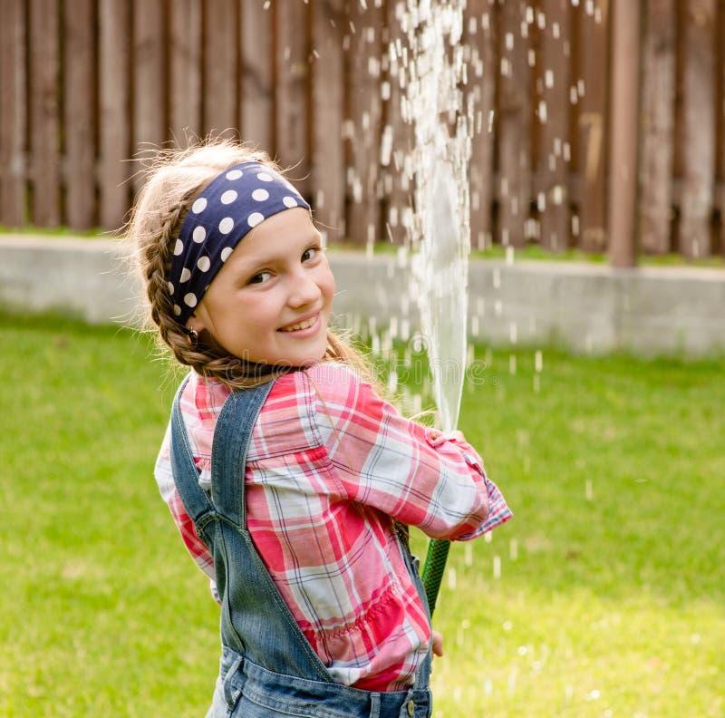 Вода счастливой милой маленькой девочки лить от шланга стоковые фотографии rf