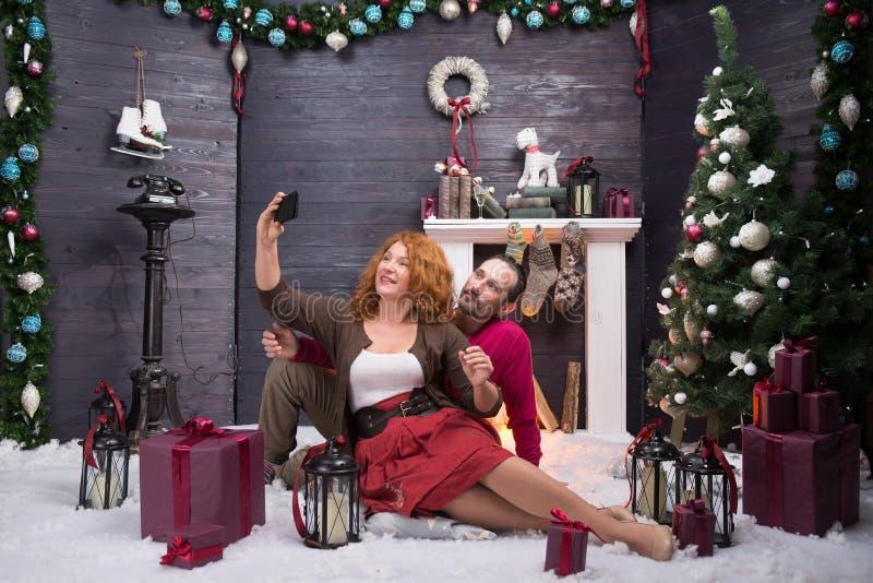 Во всю длину довольных зрелых пар делая selfie против предпосылки рождества стоковая фотография rf