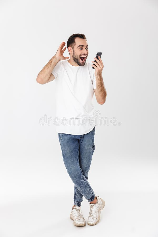 Во всю длину красивого жизнерадостного человека нося пустое положение футболки над белой предпосылкой, кричащий, держа чернь стоковые изображения rf