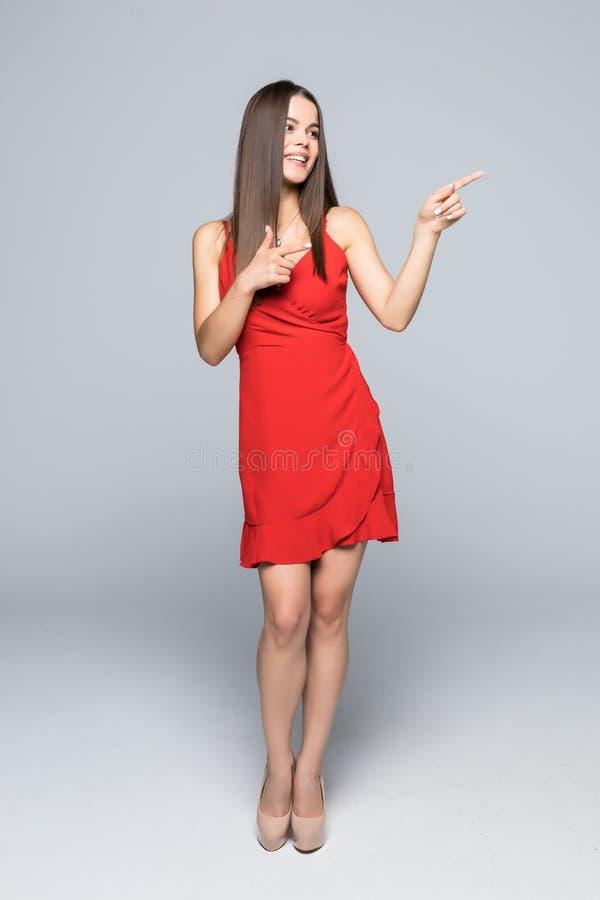 Во всю длину красивой молодой женщины в красном платье и высоких пятках стоит, представляет на что-то и смотрит прочь изолированн стоковое фото