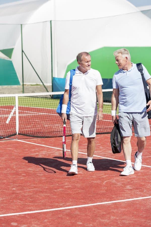 Во всю длину людей в одежде спорт говоря пока идущ на теннисный корт во время выходных лета стоковые изображения rf