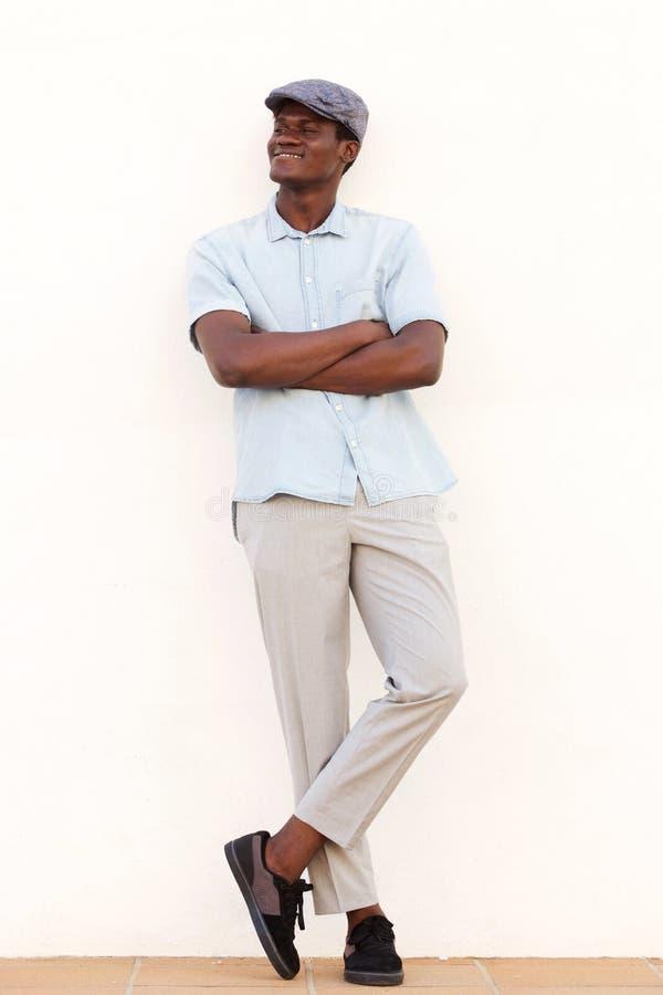Во всю длину охладите молодую африканскую склонность человека против белой стены при пересеченные оружия стоковое фото