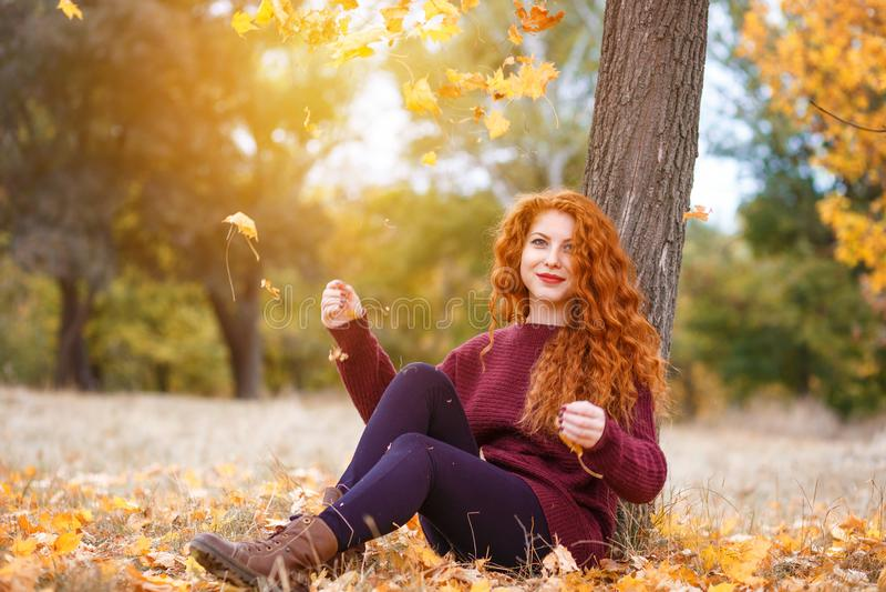 Во всю длину, счастливая красная с волосами женщина в парке осени стоковая фотография