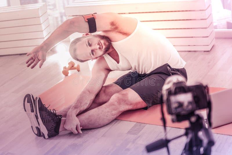 Во всю длину трудолюбивого спортсмена записывая его консультацию дома стоковая фотография
