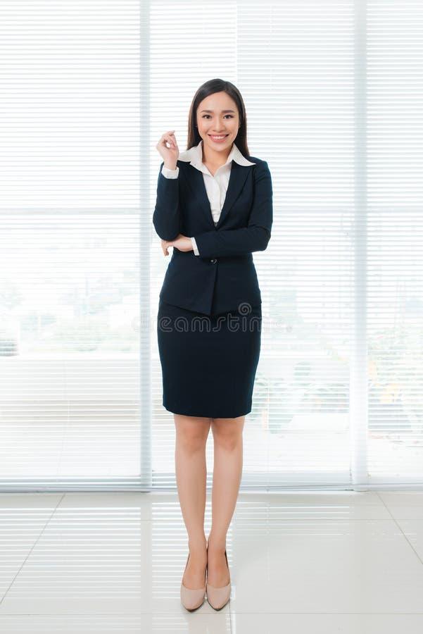 Во всю длину уверенно красивой молодой азиатской женщины смотря стоковые фотографии rf