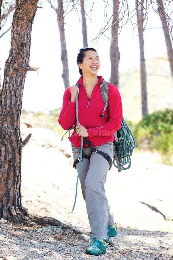 Во всю длину усмехаясь азиатский женский пеший туризм в лесе стоковое изображение rf