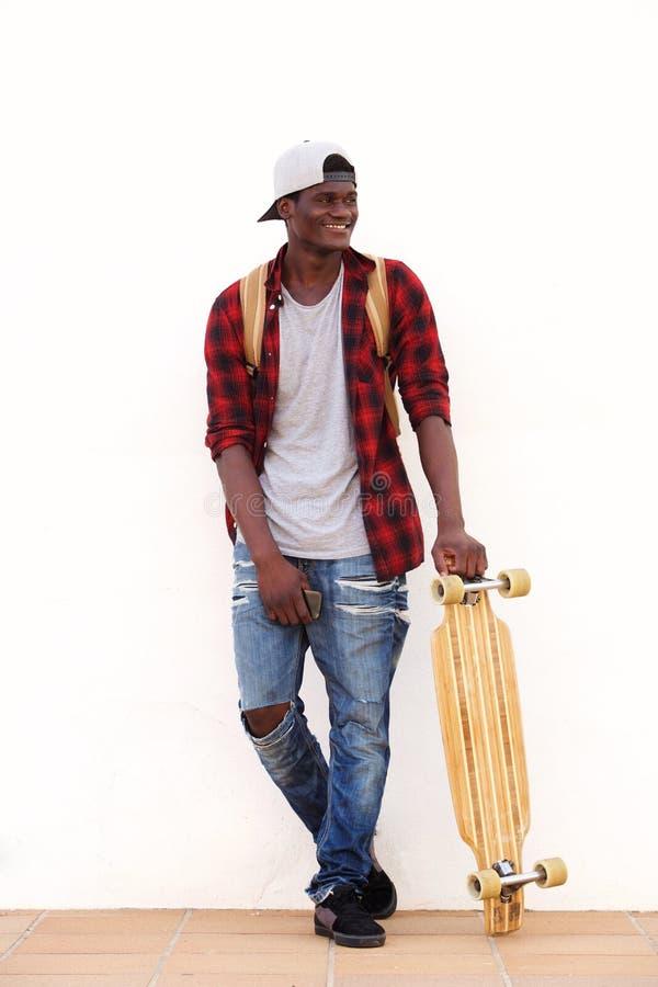 Во всю длину усмехаясь молодой парень стоя против стены с скейтбордом стоковое изображение