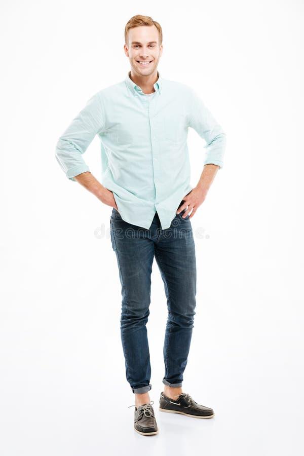 Во всю длину жизнерадостного красивого положения и усмехаться молодого человека стоковые фотографии rf