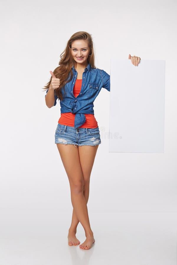 Во всю длину красивой женщины стоя позади, держащ белый bl стоковая фотография