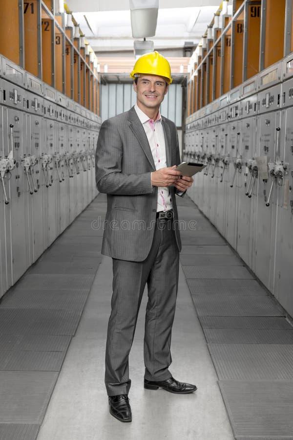 Во всю длину молодого мужского заведущей с машинами цифровой таблетки рассматривая в индустрии стоковые изображения