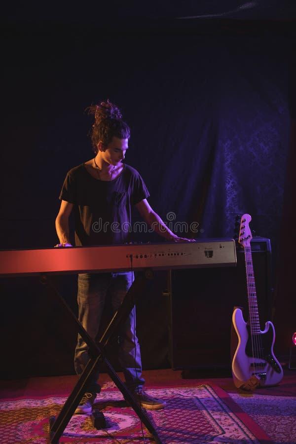 Во всю длину мужского музыканта играя рояль стоковое изображение